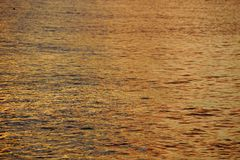 Shades of Yellow-orange Ocean Water ripples off the North Shore Stock Photo