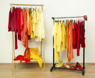Shades of yellow, orange and red clothes hanging on a rack nicely arranged. Stock Photos