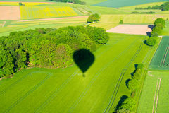 Shadow of a aerostat on green landscape from above Stock Image