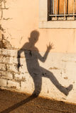 Shadow against a wall. A silhouette of a woman making a running motion on a wall royalty free stock images