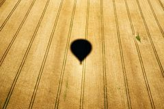 Shadow of air hot balloon. On the field stock images