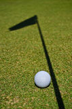 Shadow and a ball. A golf ball and the shadow of the hole flag Royalty Free Stock Photography