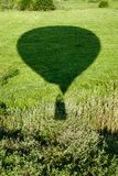 The shadow of the balloon on the background of a green meadow. royalty free stock images