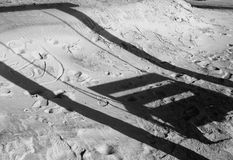 Shadow of beach bench-swing on sand. The shadow of a beach bench-swing in the sand, which has footprints and drawings on it Royalty Free Stock Photo