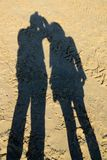 Shadow on the beach sand. The shadow lengthened as the sun went down Stock Photo