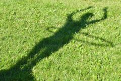 Shadow from the beautiful girl on green grass. G royalty free stock images