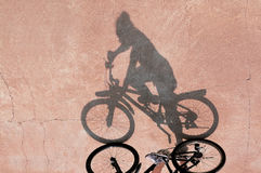 Shadow of the bicycle and the girl on an asphalt surface Stock Photography