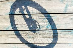 Shadow from a bicycle wheel on a wooden background.  Stock Images