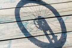 Shadow from a bicycle wheel on a wooden background.  Royalty Free Stock Images