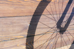 Shadow from bicycle wheel on the wooden boards Stock Image