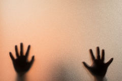 Shadow blur hands of the Man behind frosted glass.Blurry hand ab Royalty Free Stock Photography