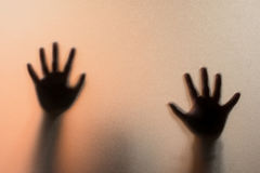Shadow blur hands of the Man behind frosted glass.Blurry hand ab Royalty Free Stock Image
