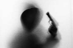 Shadow blur of horror man in jacket with hood gun in his hand.Da stock photo
