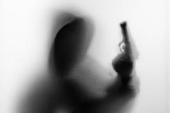 Shadow blur of horror man in jacket with hood gun in his hand.Da Stock Photo