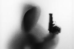 Shadow blur of horror man in jacket with hood gun in his hand.Da Royalty Free Stock Images