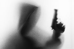 Shadow blur of horror man in jacket with hood gun in his hand.Da Royalty Free Stock Photo