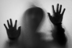 Shadow blur of horror man in jacket with hood.Hands on the glass Stock Images