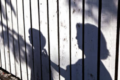 Shadow of a boy with mother. At a wooden fence Stock Photos
