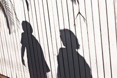Shadow of a boy with mother at a wooden fence Royalty Free Stock Photography