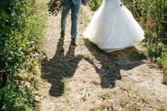 Shadow of  bride and groom walking to ceremony Stock Photos