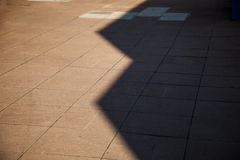 Shadow from buildings create abstract shapes on paving slabs with empty space for copy Royalty Free Stock Images