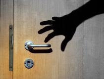 Shadow of a burglar`s hand opening a door stock photos