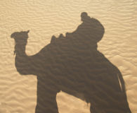 Shadow of a camel rider. Shadow of a man on camel on pristine sand Royalty Free Stock Images