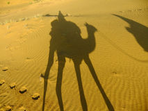 Shadow of a camel with tourist on a sand dunes, Thar desert, Ind Royalty Free Stock Images