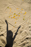 Shadow of the child and heart in the sand Royalty Free Stock Photos