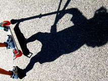 Shadow of a child riding a scooter Stock Photo