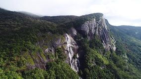 Awesome aerial shot of mountains waterfall on Adam Peak in Sri Lanka. The shadow from the clouds falls on the river that flows down the rocks of Adam`s Peak in stock video