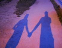 Shadow of a couple holding hands projected on the ground at night. royalty free stock photos