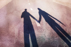 Shadow couple holding hands. Shadow of man and woman holding hands on walk on city street. Concept broken love background stock photography