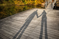 Shadow of couple holding hands. At wooden bridge. Autumn season sunny day with shadow of couple stock photo