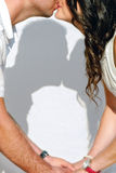 Shadow of couple kissing on white background. Young wedding couple kissing, holding hands with shadow on white background royalty free stock image