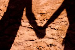 Shadow of a couple in love on the sand of the beach. Couple caught by hands in shadow on beach sand stock images
