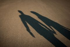 Shadow of a couple on the road holding hands. Romantic dating concept stock images