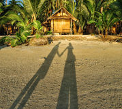 Shadow of a couple on the sunset beach near the bungalow Royalty Free Stock Images