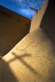 Shadow of a Cross. Shadow of the cross on the orange clay wall of the famous landmark of the adobe church in Taos with the background of blue sky Stock Photos