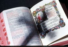Shadow of cross on bible. Shadow of the cross on open pages of the bible Royalty Free Stock Image
