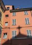 The shadow of cross. The shadow of the cross of a Christian church is reflected above in the old colorful buildings in a characteristic Italian town Royalty Free Stock Images
