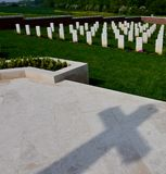 Shadow of cross and section of gravestones at Fromelles War Cemetery in northern France stock images