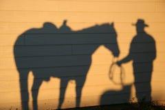 Shadow With Dog and Horse. Cowboy, horse and dog shadows on a barn at sunrise. Colorado, USA Royalty Free Stock Photos