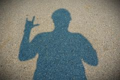The shadow that is doing the gesture. stock photography