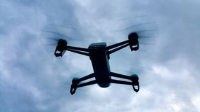 Shadow drone flying in the cloudy sky. Shadow drone flying in the blue sky with white clouds Stock Photography