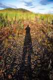 Shadow in Drought. A man's imposing shadow upon a dried up river during a drought stock photography