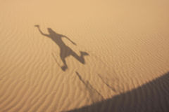 Shadow in dunes with jumping man Royalty Free Stock Photo