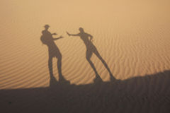 Shadow in dunes with thirsty man Stock Photo