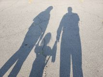 Shadow of a family on the dry pavement on a sunny day, background and texture. Shadow family dry pavement sunny day background texture love person man woman baby stock photos