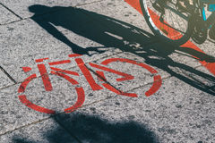 Shadow of female biker and bicycle route road marking Stock Photos